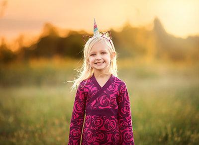 Portrait of smiling girl wearing unicorn headband with artificial ears on field - p1166m1547442 by Cavan Social