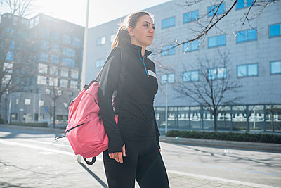 Sporty young woman walking in the city - p300m2170577 by Eugenio Marongiu
