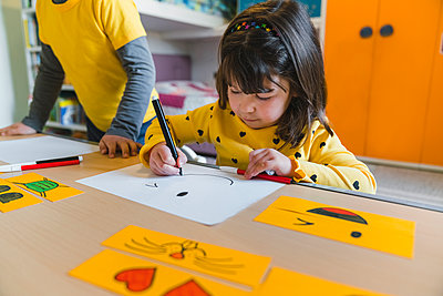 Girl drawing smiley face on paper while playing at home - p300m2282369 by Giorgio Magini