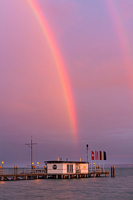 Germany, Rainbow over ferry jetty with flags at Lake Constance - p300m879299 by Holger Spiering
