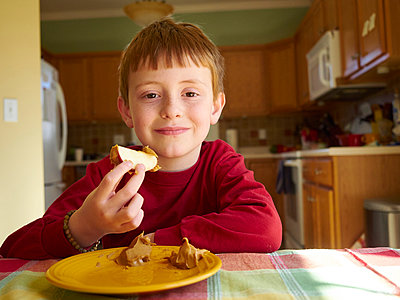 Caucasian boy eating apple with peanut butter snack - p555m1413163 by Jeff Greenough