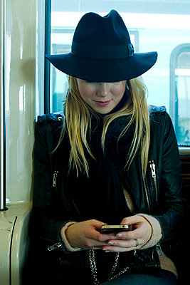 Woman using cell phone on public transportation - p675m922862 by Frederic Cirou