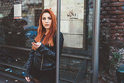 Red haired woman waiting at bus stop holding smartphone - p924m1494937 by Eugenio Marongiu