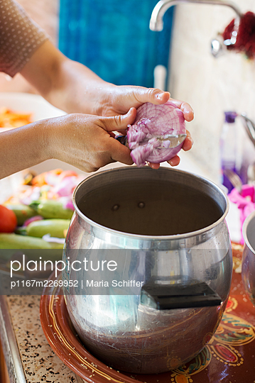 Woman cutting a red onion into a cooking pot - p1167m2269952 by Maria Schiffer