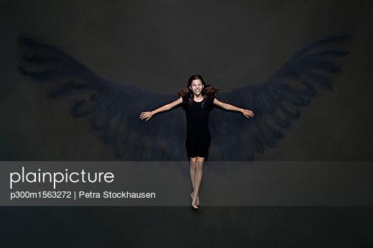 plainpicture - plainpicture p300m1563272 - Happy girl lying on painted... - plainpicture/Westend61/Petra Stockhausen