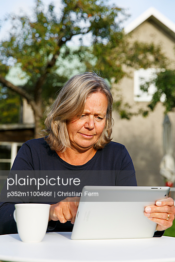 Sweden, Sodermanland, Mature woman using digital tablet at table in backyard