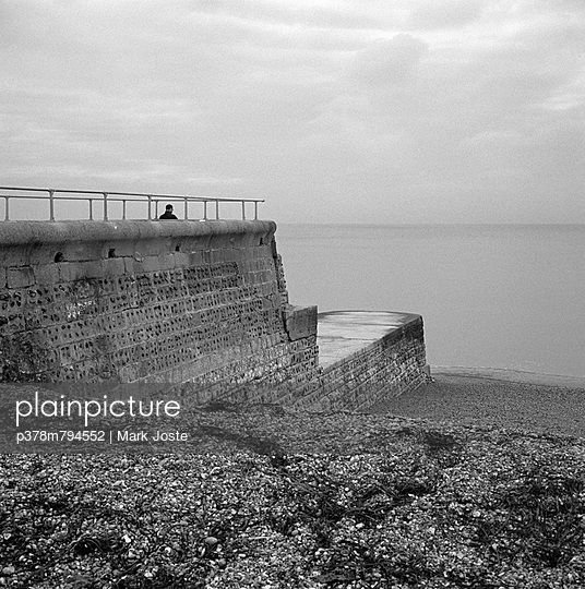 Man alone on sea defence - p378m794552 by Mark Joste
