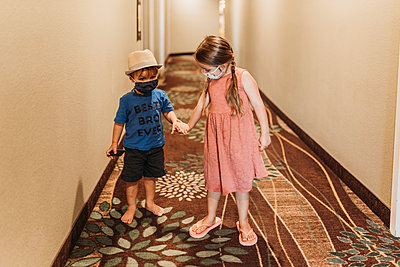 Young siblings wearing masks walking through hotel hallway together - p1166m2218292 by Cavan Images