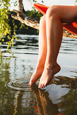 Frau taucht Fuß ins Wasser - p1396m2015026 von Hartmann + Beese