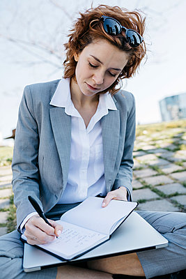Businesswoman in the city, sitting on ground, writing in notebook - p300m2103939 by Josep Rovirosa