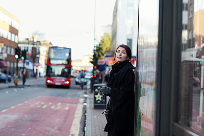 Young woman standing on bus stop - p312m927314f by Johanna Nyholm