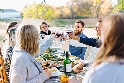 Friends toasting with wine at outdoor table - p555m1311876 by Emily Suzanne McDonald