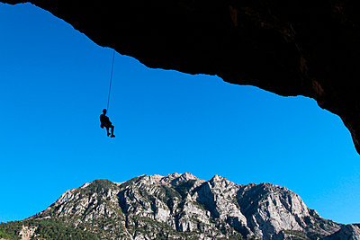 A climber lowers off a very overhanging cave climb on the cliffs above Bielsa, Spanish Pyrenees, Aragon, Spain - p8713183 by David Pickford