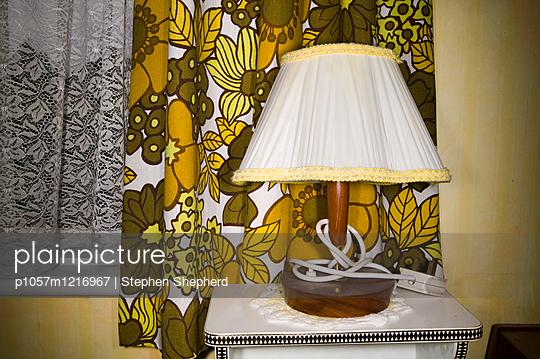 Alte Lampe vor einem Fenster mit Vorhang - p1057m1216967 von Stephen Shepherd