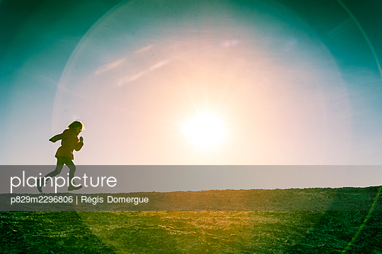 Running girl at sunset - p829m2296806 by Régis Domergue