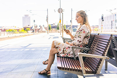 Female sitting on a bench in a railway station and using smartphone - p1332m2045756 by Tamboly