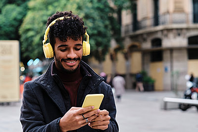 Smiling man wearing headphones using mobile phone while standing in city - p300m2250175 by Alvaro Gonzalez