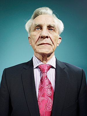 An elegant senior man wearing a suit and bright pink tie - p30120505f by Carl Smith