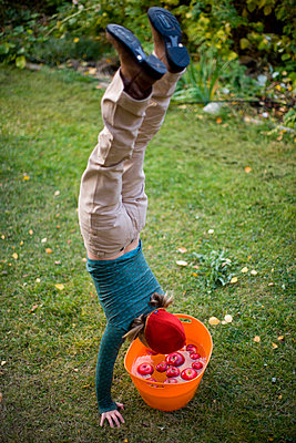 Woman does handstand over a barrel of apples. - p343m1089562 by Woods Wheatcroft