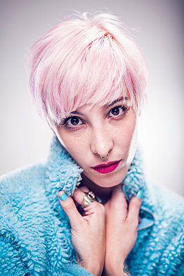 Portrait of young woman with pink hair, pulling blue jacket around neck - p429m1418290 by Celeste Martearena