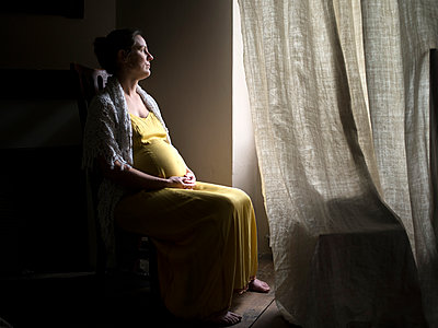Pregnant woman sits by the window - p945m1477516 by aurelia frey