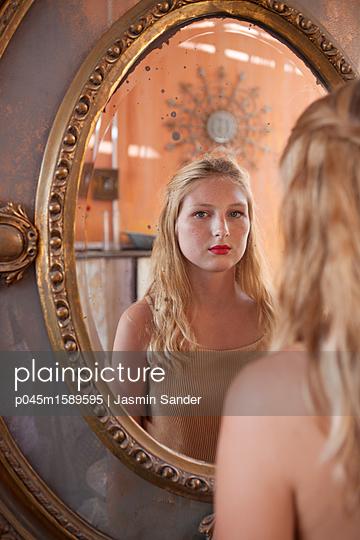 Frau schaut in Kamera über Spiegel - p045m1589595 von Jasmin Sander