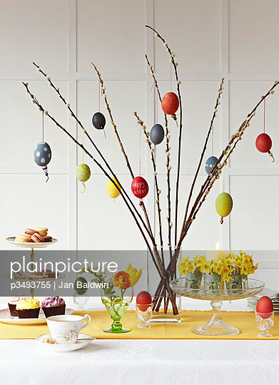 Decorated Easter Eggs tied with ribbon on pussy willow branches. Tea setting with Daffodils and candle - p3493755 by Jan Baldwin