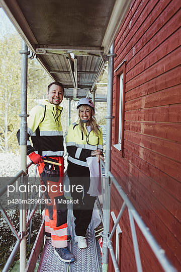 Full length of happy male construction worker with female colleague standing at scaffolding - p426m2296283 by Maskot