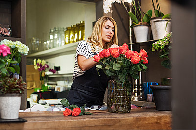 Florist arranging red roses in vase - p1166m1182701 by Cavan Images