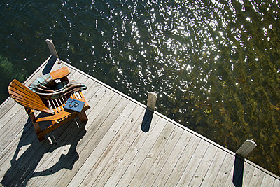 United States, New York State, Lake Placid, Overhead view of Adirondack chair book and blanket on wooden pier - p1427m2271682 by Chris Hackett
