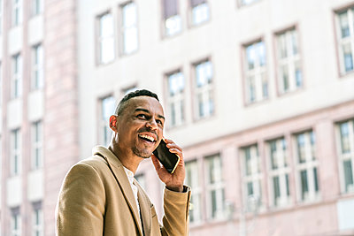 Portrait of laughing businessman on the phone in the city - p300m2143377 von Hernandez and Sorokina