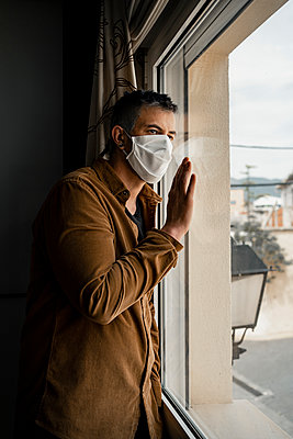 Man wearing protective mask and looking out of the window - p300m2189472 by Rafa Cortés