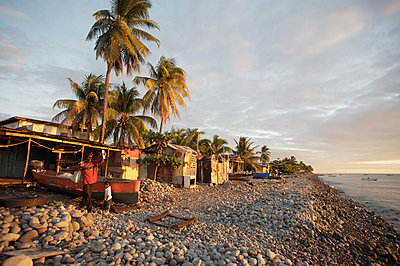 People in front of shacks on beach at sunset, Roseau,Dominica - p644m728589 by Paul Miles