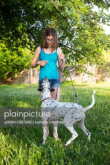 Girl teaching Dalmatian in the garden - p300m1587046 von Larissa Veronesi