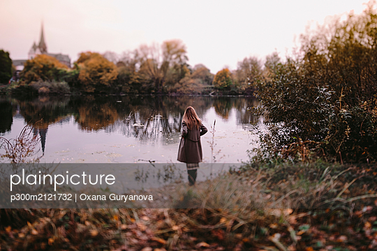 Back view of woman standing at water in autumn - p300m2121732 by Oxana Guryanova