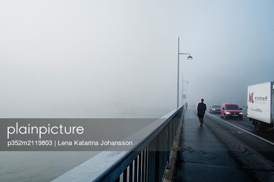 Man walking on bridge on foggy day in Stockholm - p352m2119803 by Lena Katarina Johansson