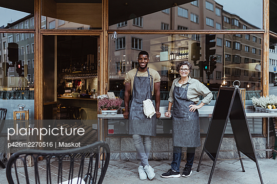 Portrait of smiling male and female coworker outside deli store - p426m2270516 by Maskot