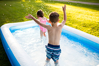 Preschool brother and sister playing and splashing in inflatable swimming pool - p1023m1486444 by Cassandra Zetta