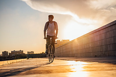 Young man with backpack riding bike on promenade at sunset - p300m2059656 by Vasily Pindyurin