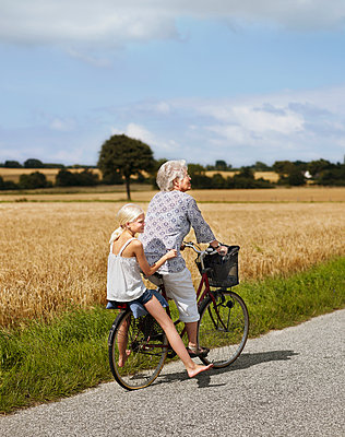 Grandmother cycling with granddaughter - p312m2200028 by Pernille Tofte