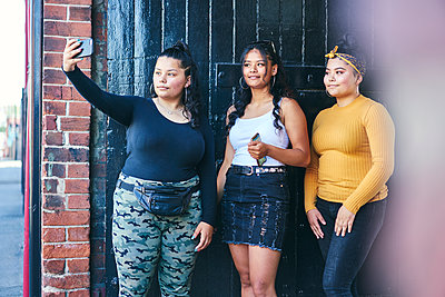 Young woman and her teenage sisters posing for smartphone selfie in building entrance  - p429m2138346 by GS Visuals