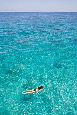 Girl swimming in ocean - p6416759f by Martin Barraud