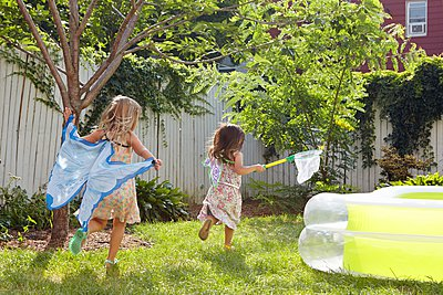 Girls in butterfly costumes playing in garden - p924m1081822f by Megan Maloy