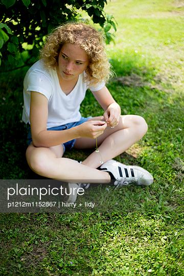 Mädchen sitzt unter dem Busch - p1212m1152867 von harry + lidy