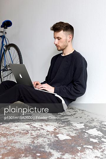Junger Mann mit Laptop Computer sitzt auf dem Fußboden - p1301m1582600 von Delia Baum