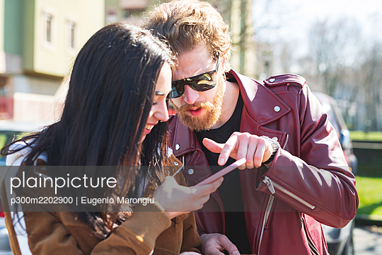 Close-up of young couple using smart phone while sitting outdoors on sunny day - p300m2202900 by Eugenio Marongiu