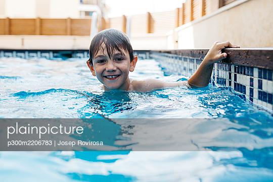 Smiling boy enjoying in swimming pool during summer - p300m2206783 by Josep Rovirosa