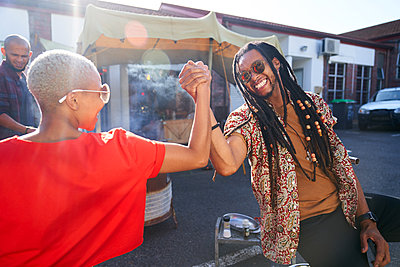 Happy friends high fiving in parking lot - p1023m2190208 by Trevor Adeline