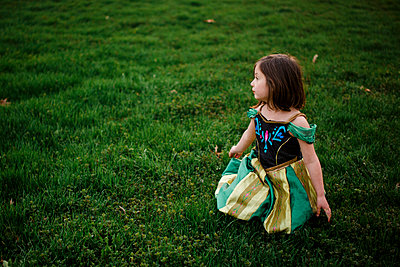 A small girl in a princess costume sits alone in a grassy field - p1166m2130179 by Cavan Images