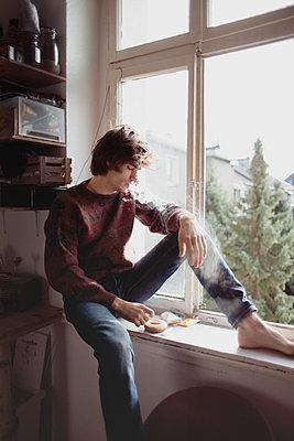 Junger Mann sitzt am Fenster  - p1429m1502599 von Eva-Marlene Etzel